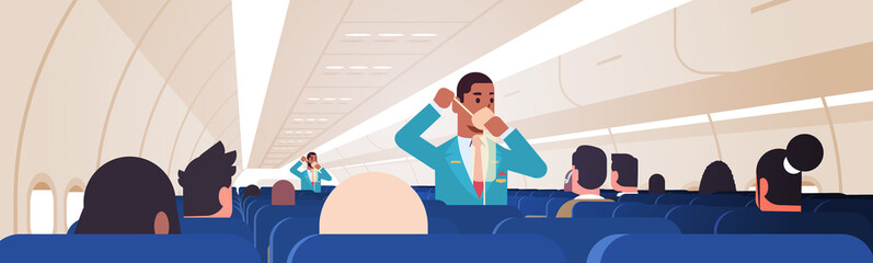 steward explaining for passengers how to use oxygen mask in emergency situation african american male flight attendants safety demonstration concept modern airplane board interior horizontal vector