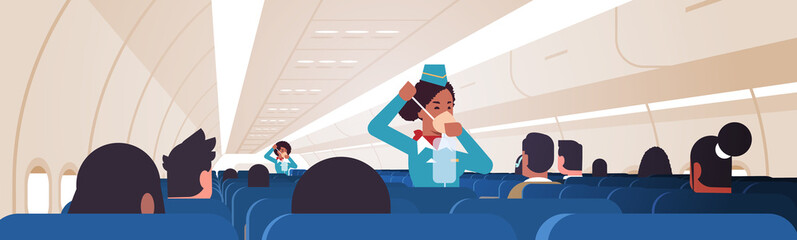 stewardess explaining for passengers how to use oxygen mask in emergency situation african american flight attendants safety demonstration concept modern airplane board interior horizontal vector