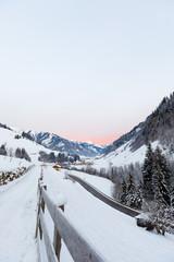 orange sunrise in valley großarl, austria in winter with snow