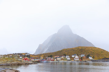 traditional red house in Norway in Reine, Lofoten with stock fish rack and mountains in background, covered in fog