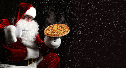 Happy laughing Santa Claus hold big hot steaming original pizza offering pointing finger. New year and Xmas fast food