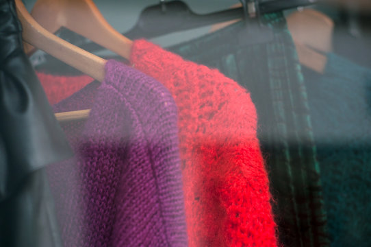 closeup of colorful woolen pullover on hangers in a woman fashion store showroom