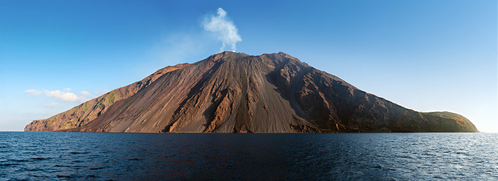 "The stromboli vulcano erupting on the ""Sciara del Fuoco"" north west side, day shot, blue sky background, panoramic shot, eolians islands, sicily, italy"