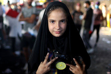 An Iraqi girl carrying a gas mask poses for a photo during the ongoing anti-government protests in Baghdad