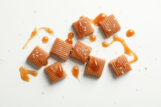 Salted caramel candies and sauce on white background, space for text