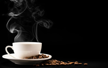 Cup coffee with steam and beans on a black background, a place for text.