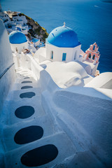 Traditional white architecture and greek orthodox churches with blue domes over the Caldera in Aegean
