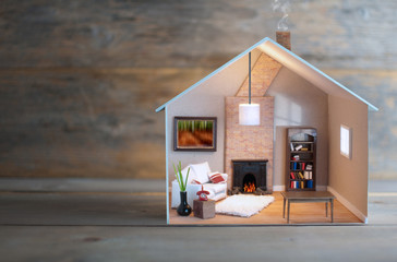Miniature house over a wooden background