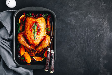 Thanksgiving baked chicken or turkey with spices, oranges and cranberries
