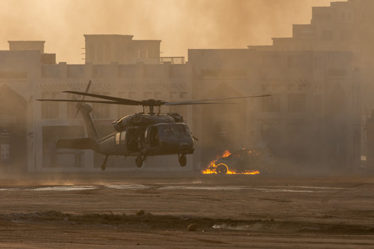 Military combat and war with helicopter landing in the chaos and destruction. Smoke and fire on the ground. Military concept of power, force, strength, air raid.