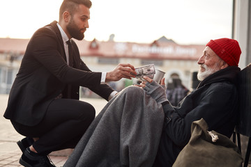 Kind man in suit hunkered down to homeless and give money donation, one dollar bill to beggar male