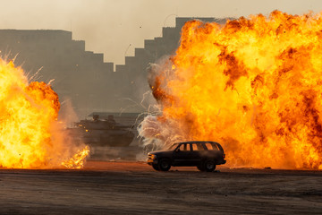 Close up of a Military strike or bomb in war on an SUV with tanks causing fire balls and explosion in the town in chaos. Military war concept. Strength, power, force, fire, explosion. Fototapete