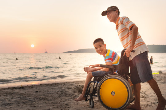 Asian special child on wheelchair is happily on the beach with father,Dad and son spend holiday to travel and learning about nature around the sea,Life in the education age,Happy disabled kid concept.