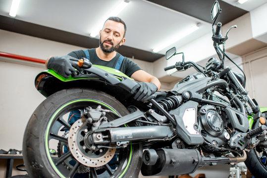 Worker repairing motorcycle in the workshop