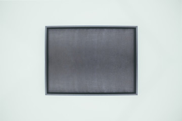 1 single solitary isolated empty blank display box frame art gallery exhibition hanging on green wall. Rectangular interior design blackboard. Black stone slate rectangle case Free vacant sign message