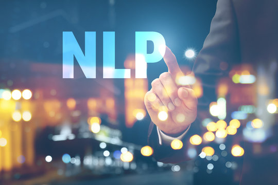 Double exposure of young businessman touching word NLP on virtual screen and illuminated city at night