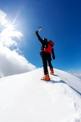 At the top: a lonely climber reaches the summit of a snowy mountain peak in winter season. European Alps.