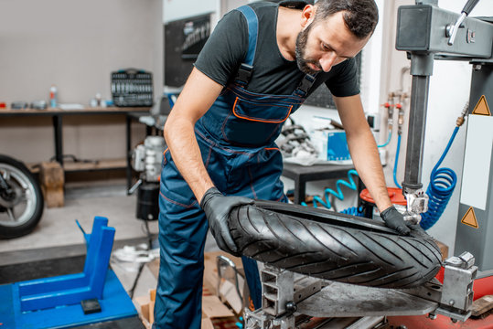 Worker changing a motorcycle tire