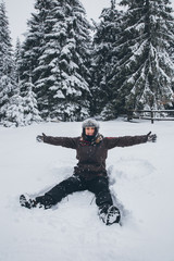 Woman doing a snow angel in heavy snow. Winter time.