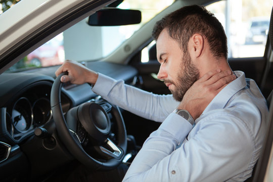 Young man rubbing his aching neck, looking tired from driving. Male driver having neck pain, sitting in his car