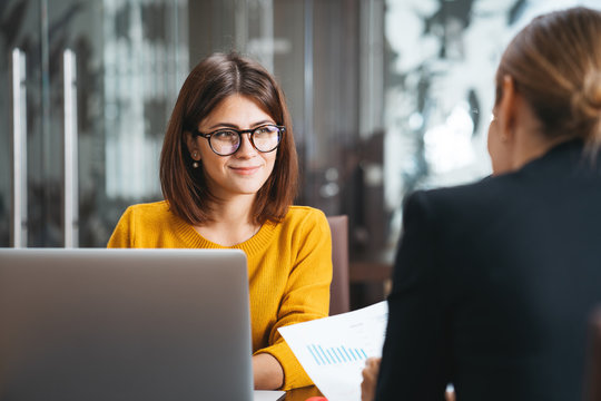 Group of happy business people have meeting at workplace in office. Two positive woman working together using modern laptop for working concept