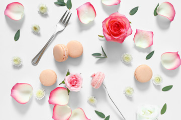 Tasty macarons with rose flowers on white background
