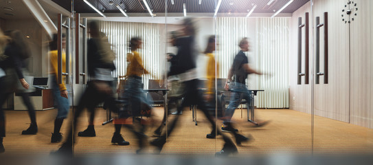 Businesspeople walking at modern office. Group of business employees at coworking center. Motion blur. Concept work process. Wide image Fotomurales