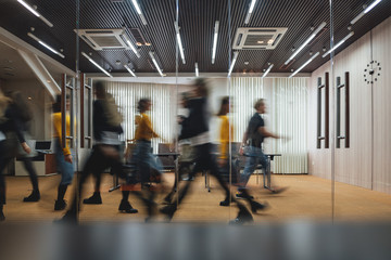Group of business people walking at modern open space. Team of business employees at coworking center. Motion blur. Concept work in process