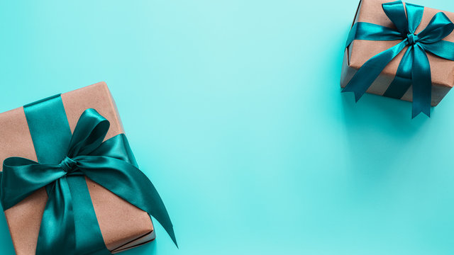 Two gift boxes in craft wrapping paper and green satin ribbon on turquoise blue background, copy space in center. Beautiful Christmas, New Year or Birthday presents, flat lay or top view. Banner