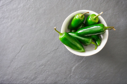 A white bowl filled with bright green jalapeno peppers rests on a gray slate cutting board