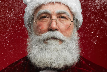 Close up portrait of fairytale Santa looking at camera with snow falling over red background