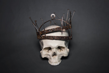 A human skull in a rusty crown, made of nails, gears and metal bands. A photo on a gray background. Postapocalypse, industrial style.