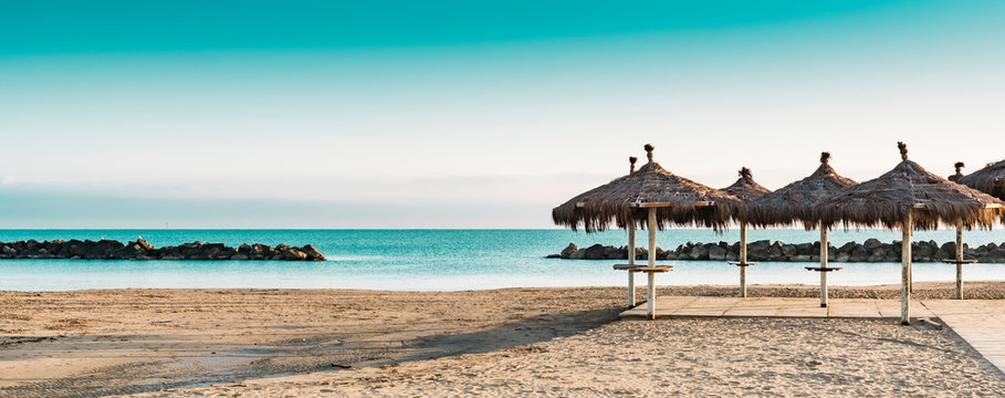 Montesilvano Beach, Italy. Wicker umbrella in sand. Panorama.