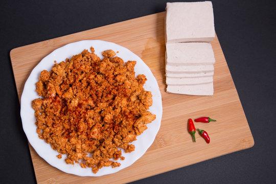 Chorizo vegano hecho con tofu firme, paprika y especias en una tabla de madera sobre fondo negro.