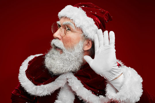 Portrait of classic Santa Claus putting hand to ear trying to hear secrets while posing against red background in studio
