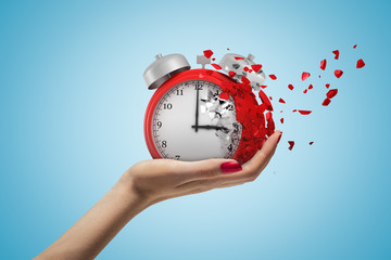 Side closeup of woman's hand facing up and holding red retro alarm clock that is dissolving into small pieces on light-blue background.