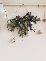 Stylish christmas tree branch with lights and glass ornaments hanging on white wall. Modern eco decoration in scandinavian style on white rural wall. Happy Holidays. Festive decor
