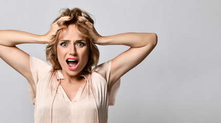 Image of excited screaming shocked beautiful woman standing isolated over light background.