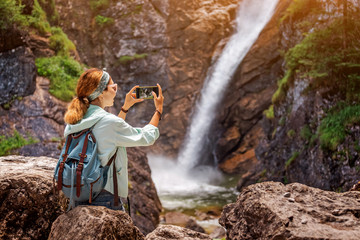 Happy traveller woman taking photo of majestic waterfall in the jungle. Hiking and sightseeing concept