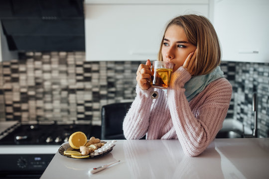 Portrait of young ill woman drinking cup of hot tea at home kitchen.