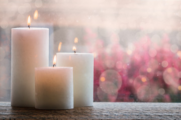 White burning candles with bokeh.