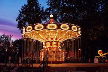 Papiers peints Attraction parc Carousel Merry go round in amusement park at evening city