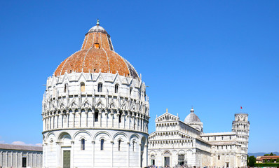 Piazza del Duomo in Pisa, Baptistery and Basilica, Italy.  Leaning Tower in the background.  Unidentifiable tourists.