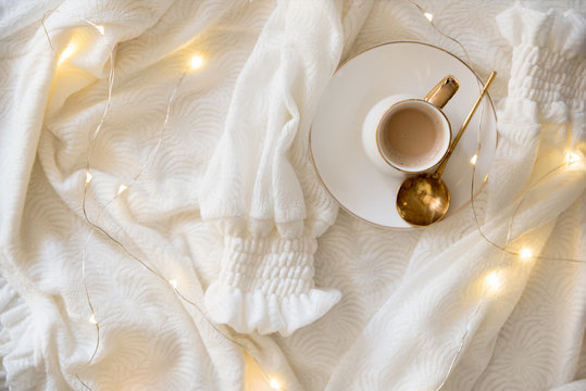 Stylish background with white glass with warm drink, beautiful white blouse and light bulbs. Suitable for winter, autumn and Christmas background.Top view