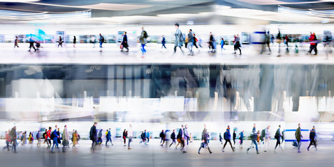 Lots of people walking on the first and second level of the transport platforms, tunnel, airport or train station. Wide panoramic view, computer generated interior.