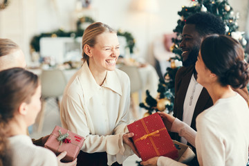 High angle portrait of elegant young people exchanging gifts and laughing happily during Christmas party, copy space