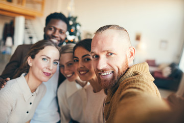 Multi-ethnic group of contemporary adult people smiling at camera while taking selfie photo during Christmas party