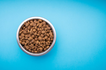 Dog food in a metal bowl. Blue background Wall mural