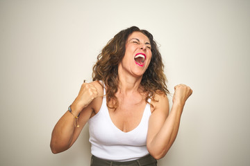 Wall Mural - Middle age senior woman standing over white isolated background very happy and excited doing winner gesture with arms raised, smiling and screaming for success. Celebration concept.