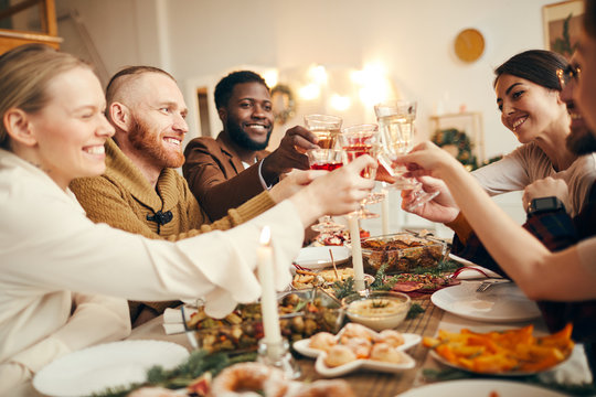 Multi-ethnic group of people raising glasses sitting at beautiful dinner table celebrating Christmas with friends and family, copy space